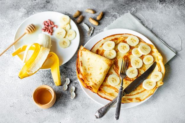 Jedzenie, deser, ciastka, naleśniki, ciasto. smakowici piękni bliny z bananem i miodem na betonowym tle