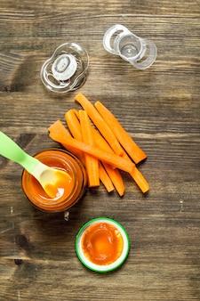 Jedzenie dla dzieci. marchewkowe puree dla dzieci z sutkiem. na drewnianym stole.