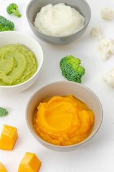 Jedzenie dla dzieci. odmiana trzech przecierów warzywnych w miseczkach. puree z dyni, przecier z kalafiora i puree z brokułów