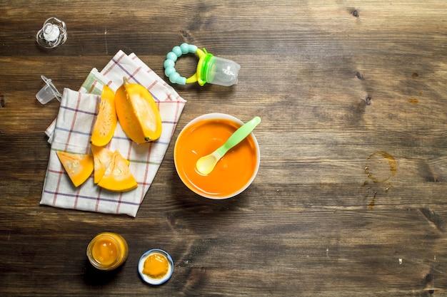 Jedzenie dla dzieci. puree dla dzieci ze świeżej dyni. na drewnianym stole.