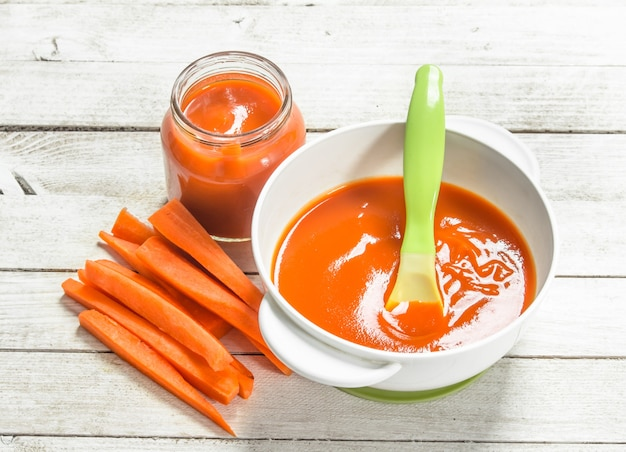 Jedzenie dla dzieci. puree dziecięce ze świeżej marchewki z łyżeczką. na białym tle drewniane.
