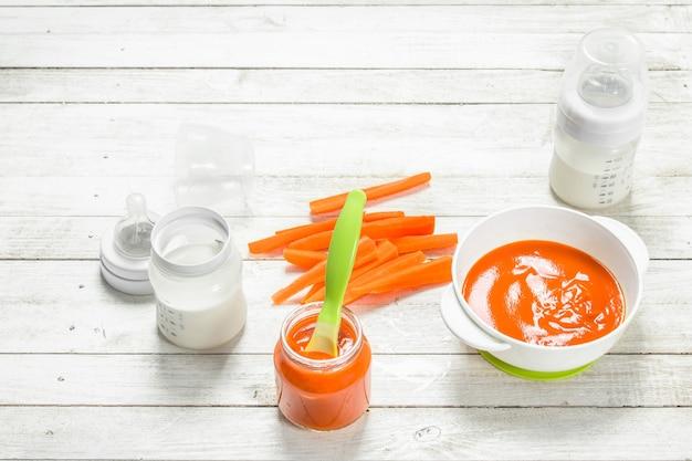 Jedzenie dla dzieci. puree z marchwi dla dzieci z mlekiem w butelce. na białym drewnianym stole.
