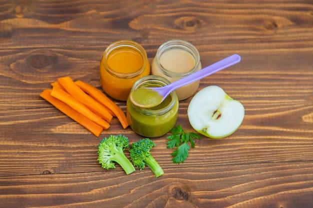 Jedzenie dla dzieci. puree z warzyw i owoców w słoikach. selektywne skupienie.