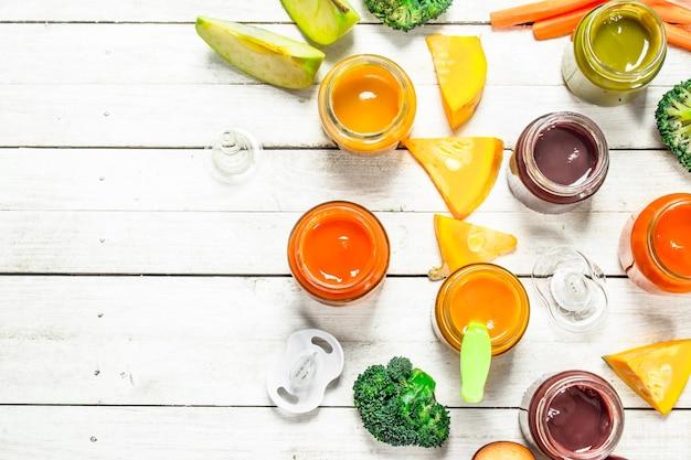 Jedzenie dla dzieci. różne przeciery dla niemowląt ze świeżych warzyw i owoców. na białym tle drewniane.