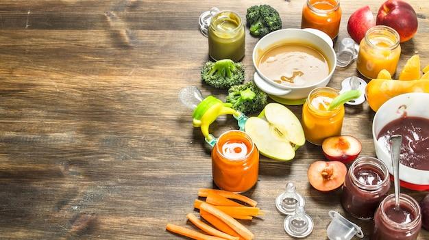 Jedzenie dla dzieci. różne przeciery z owoców i warzyw. na drewnianym tle.
