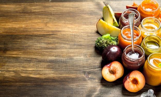 Jedzenie dla dzieci. różnorodne przeciery dla dzieci z owoców i warzyw. na drewnianym stole.
