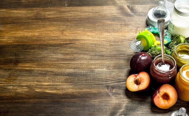 Jedzenie dla dzieci. różnorodne przeciery dla dzieci z owoców i warzyw. na drewnianym tle.