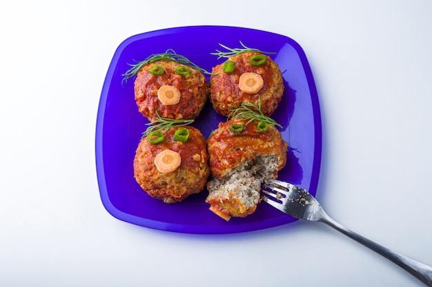 Jedzenie dla dzieci. śmieszne jedzenie. talerz z kotletami gryczanymi lub klopsikami w formie zabawnych buzi ozdobionych zieleniną