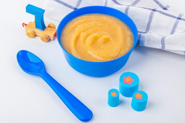 Jedzenie dla dzieci. świeży domowy mus jabłkowy. niebieska miska z przecierem owocowym na tkaninie i zabawkami dla dzieci na stole. pojęcie właściwego odżywiania i zdrowego odżywiania. żywność ekologiczna i wegetariańska