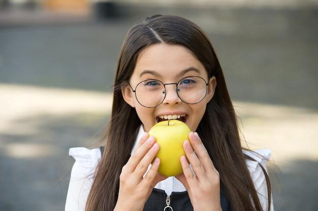 Jedzenie dla twoich zębów. małe dziecko gryzie jabłko na zewnątrz. szkolna przekąska. zdrowe odżywianie. edukacja pacjenta. zdrowie stomatologiczne. hygiena jamy ustnej. zapobieganie próchnicy i próchnicy zębów. dentysta dziecięcy.