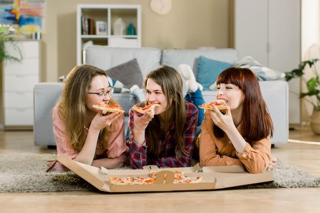 Jedzenie fast food. happy three beautiful friends laughing, eating pizza at home party. kobiety razem na obiad, ciesząc się posiłkiem. czas wolny, przyjaźń, świętowanie i ludzie pojęć