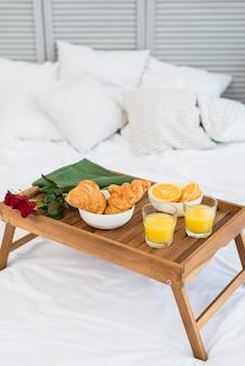 Jedzenie i kwiaty na śniadaniowym stole na łóżku
