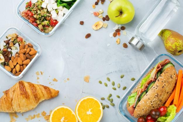 Jedzenie i picie, martwa natura, dieta i odżywianie, zdrowe odżywianie, koncepcja na wynos. pudełko śniadaniowe z kanapką, owocami, warzywami, mieszanką orzechów i butelką wody. widok z góry na płasko, skopiuj tło przestrzeni