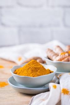 Jedzenie i picie, odżywianie dieta, koncepcja opieki zdrowotnej. surowy organiczny korzeń kurkumy pomarańczowy i proszek, curcuma longa na stole do gotowania. indyjskie orientalne przyprawy o niskiej zawartości cholesterolu. skopiuj tło przestrzeni