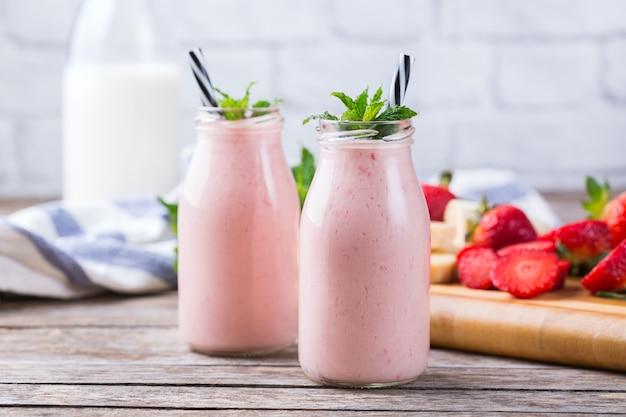 Jedzenie i picie, zdrowa dieta i odżywianie, styl życia, wegański, alkaliczny, wegetariański. różowy smoothie z bananem i truskawką na nowoczesnym stole kuchennym. skopiuj tło przestrzeni