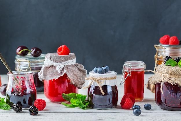 Jedzenie i picie, żniwa lato jesień koncepcja. asortyment sezonowych dżemów jagodowych i owocowych w słoikach na drewnianym stole. skopiuj miejsce rustykalne tło