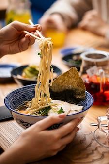 Jedzenie japońskiej zupy z makaronem shio ramen z pałeczkami
