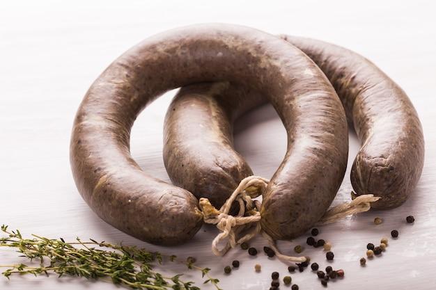 Jedzenie, mięso i pyszne pojęcie - bliska kiełbasa z mięsa końskiego z kminkiem i pieprzem na białym tle.