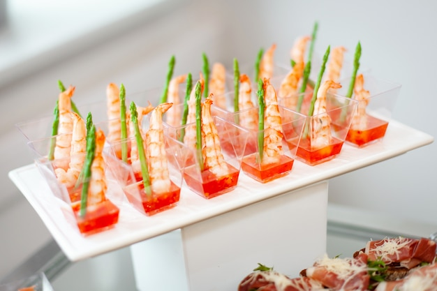 Jedzenie na imprezie: jednorazowe plastikowe kubki z przekąskami, krewetki ze szparagami i sosem słodko-kwaśnym.