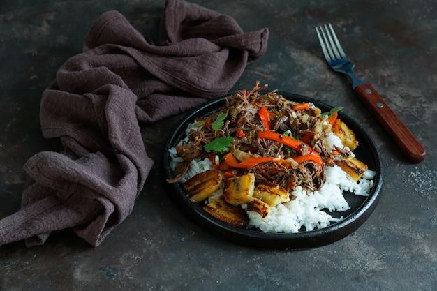 Jedzenie na kubie, rozdrobniona wołowina. jedzenie w ameryce łacińskiej. ropa vieja ze smażonymi bananami i ryżem.
