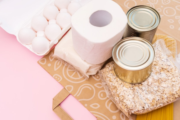 Jedzenie na okres izolacji kwarantanny na płasko leżało na żółtej przestrzeni z miejsca kopiowania. jajka, makaron, fasola, papier toaletowy, jabłko i niektóre uszczelki.