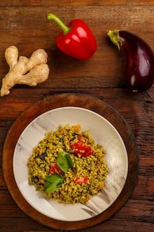 Jedzenie na suhoor w ramadan bulgur post z warzywami w talerzu na drewnianym stole obok warzyw na desce. zdjęcie pionowe
