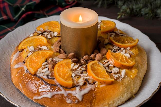 Jedzenie na święto trzech króli z plastrami pomarańczy z zapaloną świecą