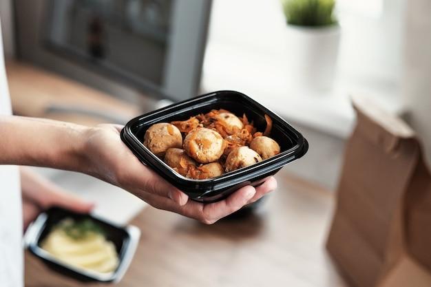 Jedzenie na wynos. kobiece ręce trzymają miskę mięsnych klopsików