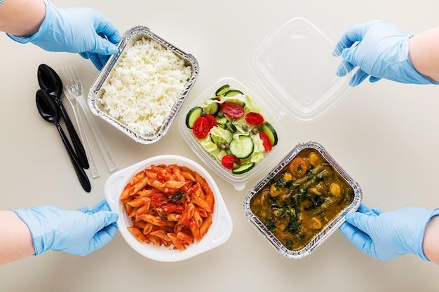 Jedzenie na wynos w jednorazowych opakowaniach. jedzenie na wynos w jednorazowych pojemnikach ryż, warzywne curry, włoski makaron z sosem pomidorowym i świeża zdrowa sałatka. i ręce w medycznych rękawiczkach chirurgicznych.