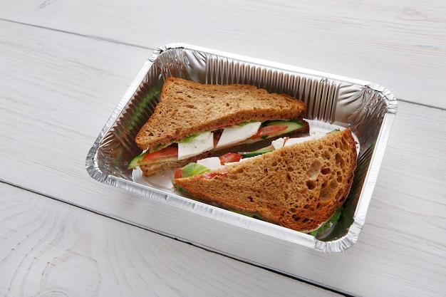Jedzenie na wynos w pudełkach foliowych. kanapki z pieczywem pełnoziarnistym, ogórkiem, serem feta i pomidorami na białym drewnie