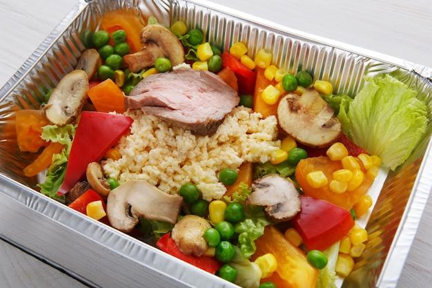 Jedzenie na wynos w pudełkach foliowych. kuskus z pieczarkami, mięsem z indyka i warzywami na białym drewnie