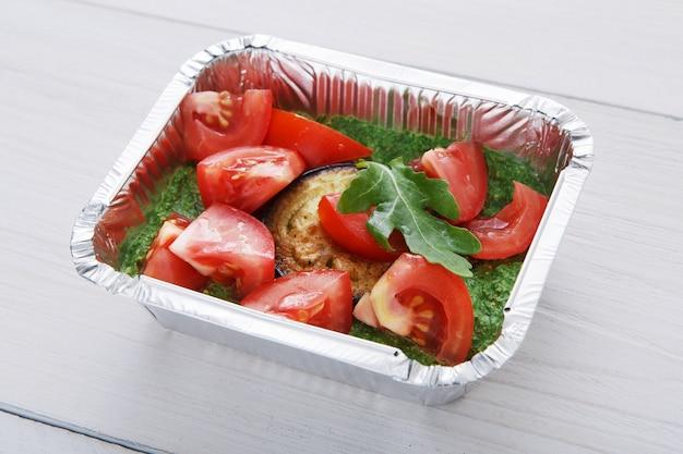 Jedzenie na wynos w pudełkach foliowych. pieczony bakłażan z guacamole i świeżymi pomidorami na białym drewnie