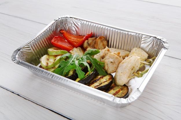 Jedzenie na wynos w pudełkach foliowych. plastry mięsa z indyka z pieczonym grillowanym bakłażanem lub bakłażanem i pomidorami na białym drewnie
