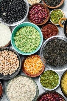 Jedzenie organiczne. asortyment roślin strączkowych w misach na rustykalnym stole.