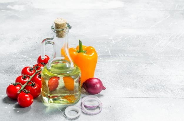 Jedzenie organiczne. dojrzałe warzywa z oliwą z oliwek. na rustykalnym tle.