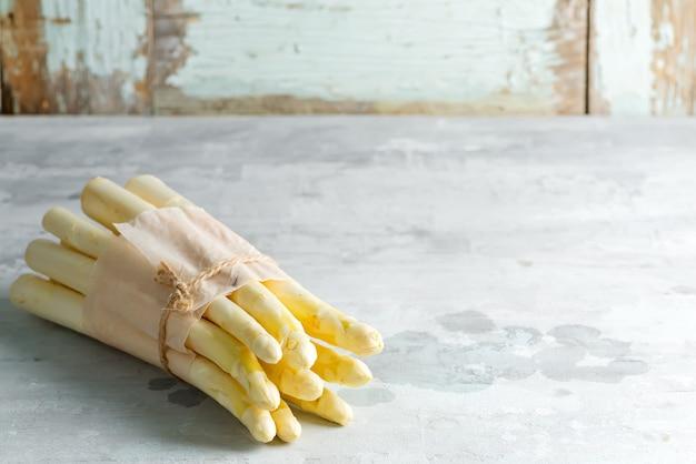 Jedzenie organiczne. koncepcja gotowania zdrowej żywności. niegotowane świeżo zebrane surowe łodygi białych szparagów organicznych na tle kamienia.
