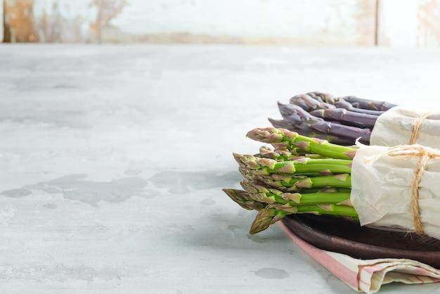 Jedzenie organiczne. koncepcja gotowania zdrowej żywności. świeża naturalna zieleń i purpurowe organicznie szparagowe dzidy jarzynowe w talerzu na kamiennym tle. widok z góry.