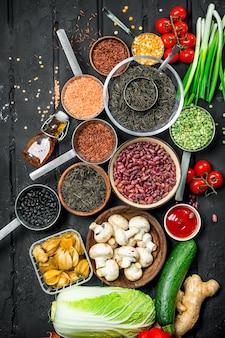 Jedzenie organiczne. odmiana zdrowych owoców i warzyw z roślinami strączkowymi na ciemnym rustykalnym stole.