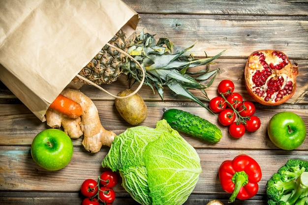 Jedzenie organiczne. opakowanie zawiera zdrowe warzywa i owoce. na drewnianym tle.