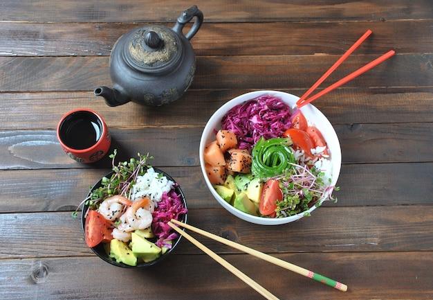 Jedzenie organiczne. przepis na świeże owoce morza. świeży łosoś szturcha miskę z ryżem, świeżą czerwoną kapustą, awokado, pomidorami cherry, ogórkiem, kiełkami rzodkiewki na drewniane tła. miska poke koncepcja żywności