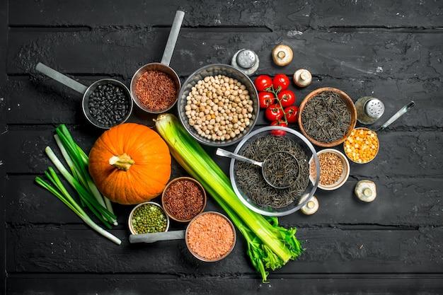 Jedzenie organiczne. różne rodzaje owoców i warzyw z roślinami strączkowymi. na czarnym rustykalnym stole.