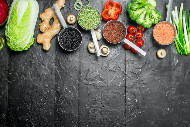 Jedzenie organiczne. różne zdrowe warzywa i owoce z fasolą. na czarnym tle rustykalnym.