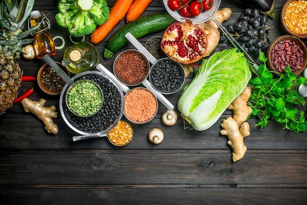 Jedzenie organiczne. różnorodność zdrowych owoców i warzyw z roślinami strączkowymi. na drewnianym tle.