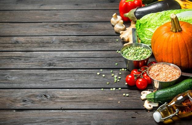 Jedzenie organiczne. świeże warzywa i przyprawy z roślinami strączkowymi. na drewnianym tle.