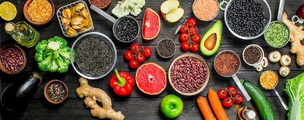 Jedzenie organiczne. świeże warzywa i przyprawy z roślinami strączkowymi na rustykalnym stole.