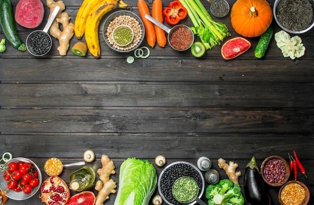 Jedzenie organiczne. zdrowy asortyment warzyw i owoców z roślinami strączkowymi. na drewnianym tle.
