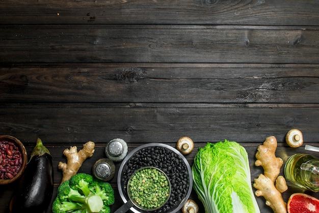 Jedzenie organiczne. zdrowy asortyment warzyw i owoców z roślinami strączkowymi na rustykalnym stole.