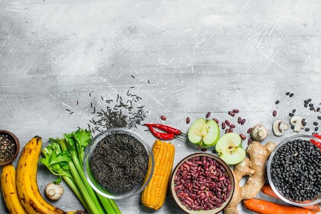 Jedzenie organiczne. zdrowy asortyment warzyw i owoców z roślinami strączkowymi. na rustykalnym tle.