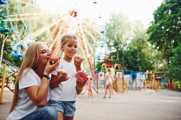 Jedzenie pączków. wesoła dziewczynka na wrotkach i jej mama wspólnie bawią się w parku przy atrakcjach.