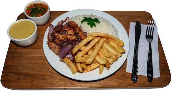 Jedzenie peruwiańskie kurczak saltado, frytki, kurczak sezonowany, cebula, pomidory, pieczone warzywa, białe arros na białym talerzu.